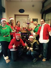 Staff at PKAVS around their Sholach Tree on Christmas Jumper day.